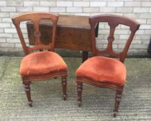 A pair of mahogany dining chairs and a pad foot drop leaf table