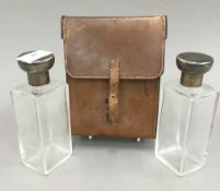 A pair of leather cased silver topped glass flasks
