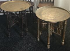 Two Eastern brass topped folding coffee tables