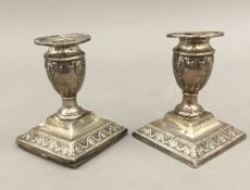 A pair of silver dwarf candlesticks (23.