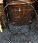 A glass topped wrought iron folding garden table