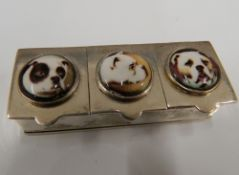 A silver pill box depicting three dogs