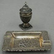 A silver pepper and an ashtray