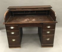 An early 20th century oak roll top desk