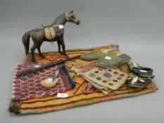 A collection of ethnographic items, including tapestry shoes, etc.