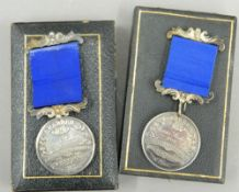 A cased silver medal and another