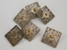 A set of six white metal filigree buttons