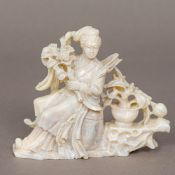 A Chinese carved hardstone figure of Guanyin Modelled seated holding flowers with a further vase of