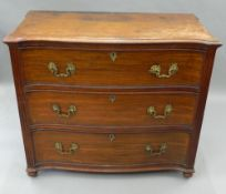 A George III mahogany serpentine chest of drawers The eared shaped top above three drawers flanked