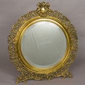 A large 19th century pierced brass strut mirror The circular bevelled mirror plate surrounded by