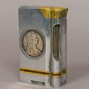 A large brass and steel table lighter Inset to either side with a silver coin. 10.5 cm high.
