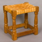 ROBERT MOUSEMAN THOMPSON of KILBURN An adzed oak stool with a tan lattice work seat,