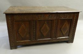 A 17th century oak coffer The rectangular plank top above a lunette carved frieze and three panels,