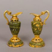 A pair of 14K gold mounted hardstone ewers Each with stylised dolphin form handle. Each 12 cm high.
