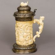 A 19th century unmarked silver mounted carved ivory stein The hinged embossed lid set with a