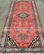 A red ground Hamadan runner 311 x 108 cm.