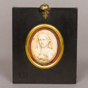 A 19th century carved ivory panel Of oval form, carved as the Virgin Mary,