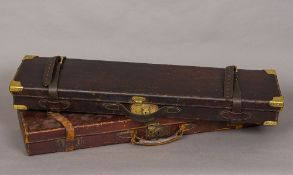 Two vintage leather gun cases One set with brass corners, each lid initialled.