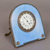 A Cartier guilloche enamel decorated silver strutt clock The white enamelled dial with Roman and