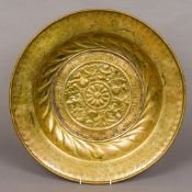 A 17th century Art brass alms dish With repousse and engraved decoration. 42.5 cm diameter.