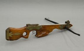 A 17th/18th century German style crossbow Formed from walnut, set with brass mounts. 88 cm long.