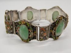 A Chinese silver and enamel five stone apple jade bracelet. Approximately 16 cm long.