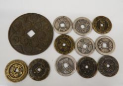 A quantity of Chinese coins and a disc. Coins 3.25 cm diameter; disc 7 cm diameter.