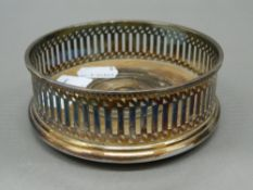 Two plated coasters and a snuffer. Coasters 11 cm diameter; snuffer 19 cm long.