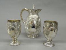 A silver jug and two silver goblets.