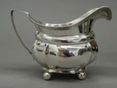 A silver cream jug. 14 cm wide (4.