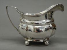 A silver cream jug. 14 cm wide (4.