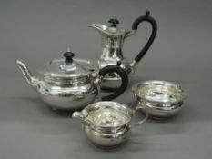 A silver four piece tea set. Coffee pot 18 cm high (25.