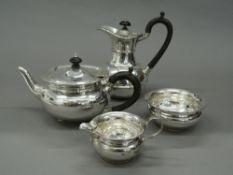 A silver four piece tea set. Coffee pot 18 cm high (25.