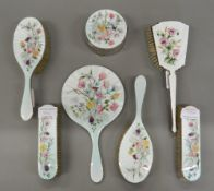 A silver and enamel dressing table set. Mirror 25.5 cm long.