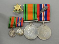 A pair of WWII medals with ribbons (1939-1945 Service Medal and The Defence Medal) and miniatures;