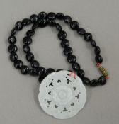 A Chinese jade pendant on necklace. 5 cm diameter.
