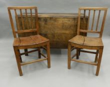 A 19th century oak drop leaf table and two 19th century solid seated chairs. The table 113 cm wide.