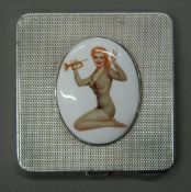A silver compact decorated with a skimpily clothed woman. 6 cm wide (67.