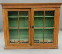 A Victorian glazed pine cabinet. 135 cm wide.