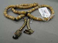 A small Tibetan necklace. Approximately 58 cm long, each disc approximately 0.75 cm diameter.