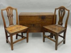 A 19th century oak drop leaf table and two 19th century solid seated chairs. Table 104 cm wide.