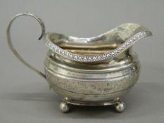 A small silver cream jug. 13 cm wide (3.