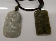 Two boxed jade pendants. Each approximately 4 cm high.