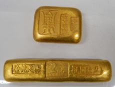 Two golden paperweights. 9.75 x 2 cm and 4.5 x 3.5 cm.