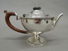A silver teapot. 15 cm high; 21 cm wide (10.
