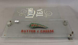 A vintage glass advertising panel for New Zealand Butter and Cheese and a glass panel with Lyons