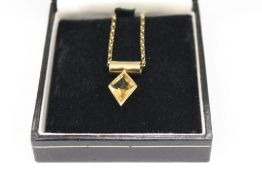 A 9 ct gold and citrine pendant, suspended by a 9 ct gold chain. The pendant 2.5 cm high (6.