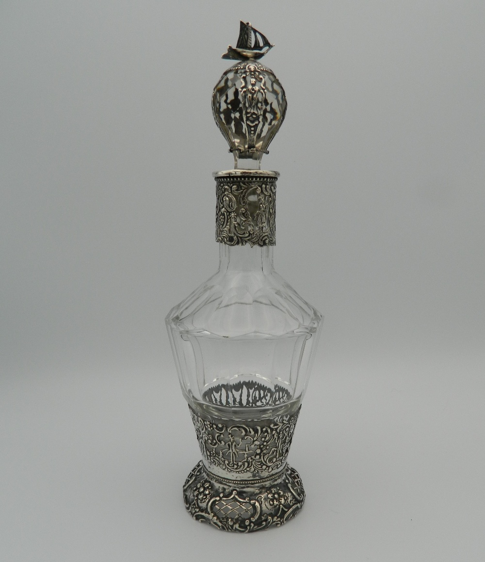 A Continental silver and cut glass decanter and stopper, the silver applied with figures,