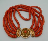 An 18 ct gold mounted five strand coral necklace.