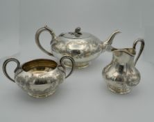 A Victorian silver three piece chased tea set. The tea pot 27 cm long (34.